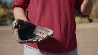 Close Up of Man Wearing Red Sweater Tossing Baseball into Gloved Hand During Casual Baseball Game in Sunny Field in Summer 4K