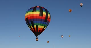 Close up of one multi color hot air balloon flying through the sky