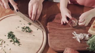 Close-up of unrecognizable woman and girl preparing food while cutting chopping onion and garlic. Shot from above