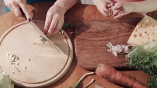 Close-up of unrecognizable woman and girl preparing healthy food cutting onion and garlic on the wooden chopping board. Shot from above