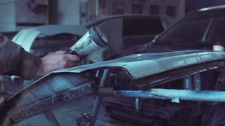 Close up of worker preparing car for painting in workshop