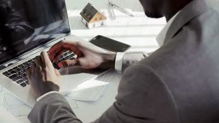 Close up of young black businessman hands typing on laptop computer keyboard in white modern office in the sunny day