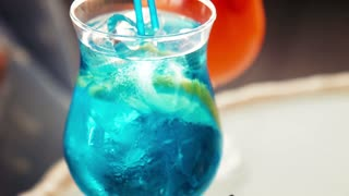 Close up on icy cold blue beverage with fruit slice and matching straw with copy space