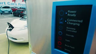 Close up on power plug station for electric automobile with car connected in background, variable point of focus
