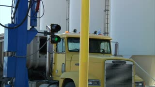 Close-up On Semi Truck Pulling Through Industrial Machinery