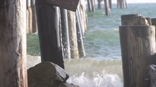Close up on water crashing under the dock