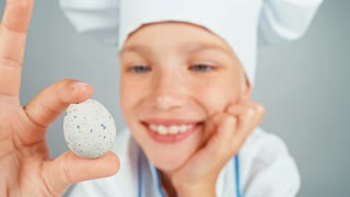 Close up portrait chef cook girl holding small quail eggs and smiling at camera