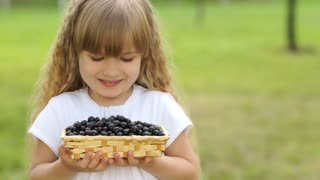 Close-up portrait of girl holding a basket of black currant