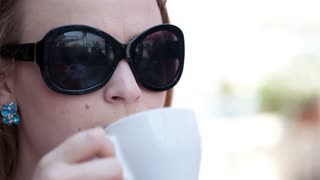 Close up portrait of young woman in sunglasses drinking coffee in the street cafe