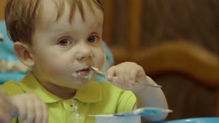 Close-up shot of a little boy eating cream yogurt with two spoons sitting at feeding table. His face is dirty with dairy