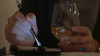Close-up shot of a woman in cafe drinking white wine and using smart phone with pen