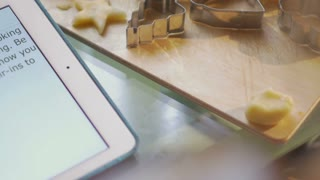 Close-up shot of a woman making cookies checking recipe on tablet computer. She cutting out a star shape from the dough