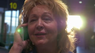 Close-up shot of cheerful senior woman talking on cell phone at the airport terminal
