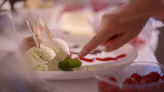 Close-up shot of chefs hands making finishing touches in dessert presentation