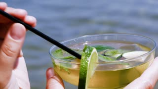 Close-up shot of drinking mojito cocktail with straw on the beach. Refreshment on a hot day. Summer vacation