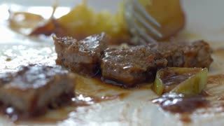 Close-up shot of eating a dish with baked potatoes, fried meat and sauce. Having a tasty dinner at home or restaurant