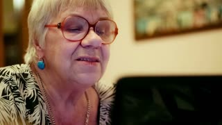 Close-up shot of emotional senior woman in glasses having a video chat using laptop