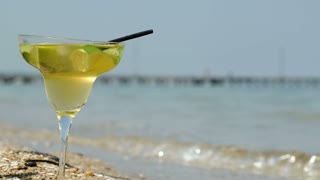 Close-up shot of hand putting lime slice on glass of cocktail standing on the beach by sea