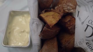 Close-up shot of hand taking baked potatoes and putting it into cream sauce