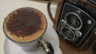 Close-up shot of pouring sugar into coffee and stirring up the foam, then taking foam with a spoon. Coffee cup standing near retro photo camera