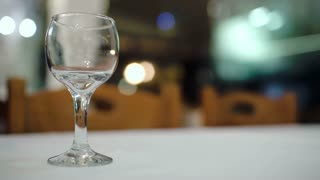 Close-up shot of pouring white wine into glass on the table in restaurant. Alcoholic drinks