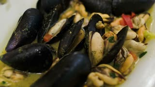 Close-up shot of spoon in delicious dish with mussels. Mediterranean cuisine