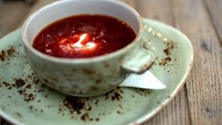 Close-up shot of stirring up sour cream in borsch served in cafe or restaurant