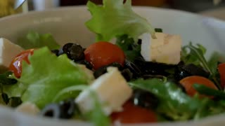 Close-up shot of tossing Greek salad with fork and spoon. Delicious vegetarian food. Cooking at home or dining in restaurant