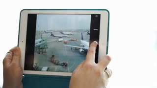 Close-up shot of woman using touch pad for taking pictures of airport area with planes and trucks through the window