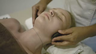Close-up shot of young woman enjoying spa neck massage with stones. Therapy at beauty spa