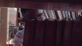 Close up shot through the bookshelf of young African-American man in glasses looking through books, searching for right literature