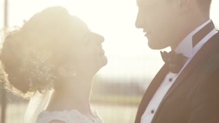 Close up view of elegant wedding couple looking at each other in a bright sunshine, bridegroom kisses her nose, cheek and neck. Touching noses. Wedding day, happy moments.