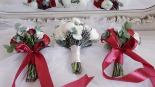 Close up view of wedding bouquets lying on the white satin material. White roses with peons for a bride. Red roses tied with red band for bridesmaids. Wedding preparation, wedding portrait.