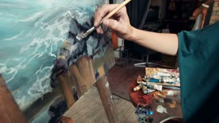 Close up woman artist working in her studio with a closeup side view of the canvas on an easel and her hand mixing paints on a palette. Woman the artist draws a picture of sea
