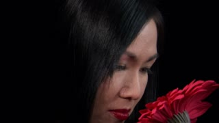 Closeup of Asian Woman Smelling Red Flower