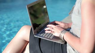 Closeup of businesswoman working with notebook by the swimming-pool