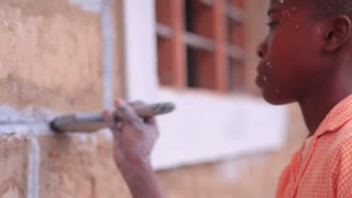 Closeup of Child Painting the Outside of a Building