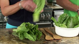 Closeup of Couple Preparing a Salad in the Kitchen