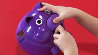 Closeup of Eight Year Old Girl Putting Money in Piggy Bank