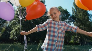 Closeup playful portrait girl walking at camera with balloons in the park