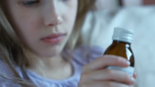 Closeup portrait child wich holding a bottle of pills