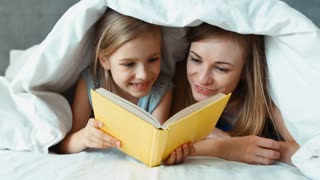Closeup portrait family mother and daughter reading book under the blanket and laughing. Zooming