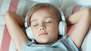 Closeup portrait girl child listening music in headphones and lying on the bed and resting. Zooming