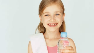 Closeup portrait girl child sportsman showing bottle of water. Thumb up. Ok