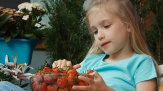 Closeup portrait girl holding a huge plate of strawberries and eating it with relish and looking at camera. Zooming