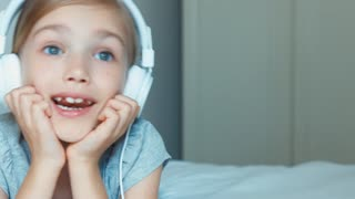 Closeup portrait girl listening music in headphones and singing a song. Child lying resting on the bed and smiling
