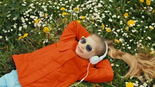 Closeup portrait girl listening to music. The child lying on the grass among flowers. Panning and zooming