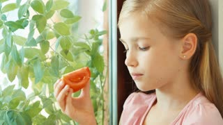 Closeup portrait girl sniffing tomato against window and nods at camera