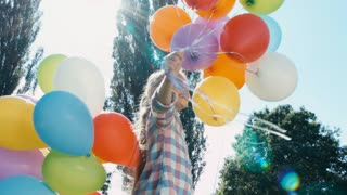 Closeup portrait with Lens flare. Girl spinning with balloons and looking at camera against the sun