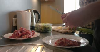 Closeup shot of a kitchen counter. Couple is preparing meal, cutting raw meat and fresh leek.